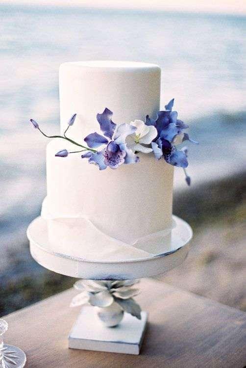Mavi ve Mor Şeker Hamurundan Çiçeklerle Süslenmiş Beyaz Pasta