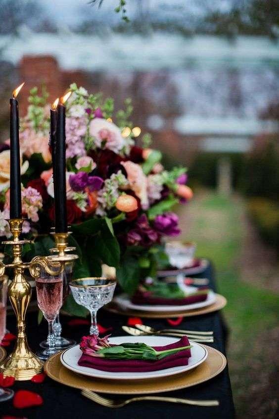 Siyah Mumlar ve Mor Tonlarında Çiçek ve Aksesuarlarla Süslenmiş Masa